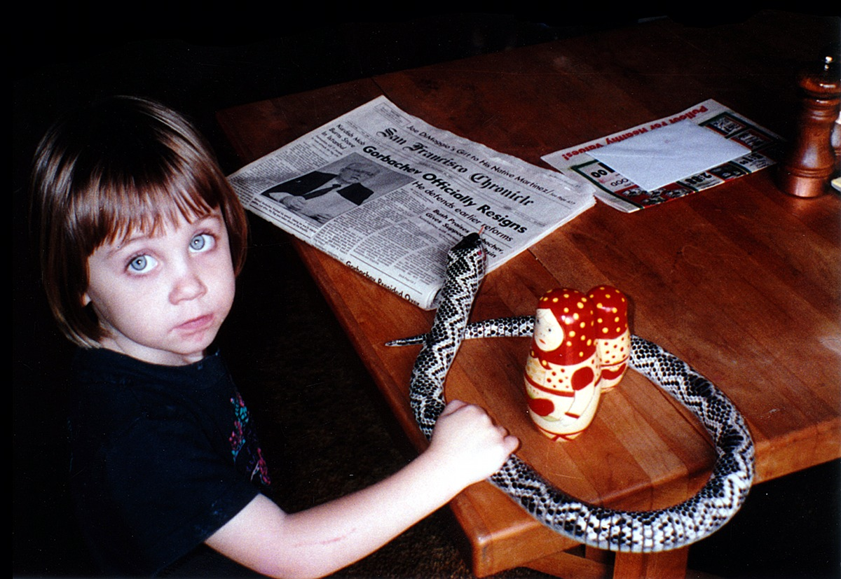 Photo of a little girl playing with Russian dolls and a toy snake